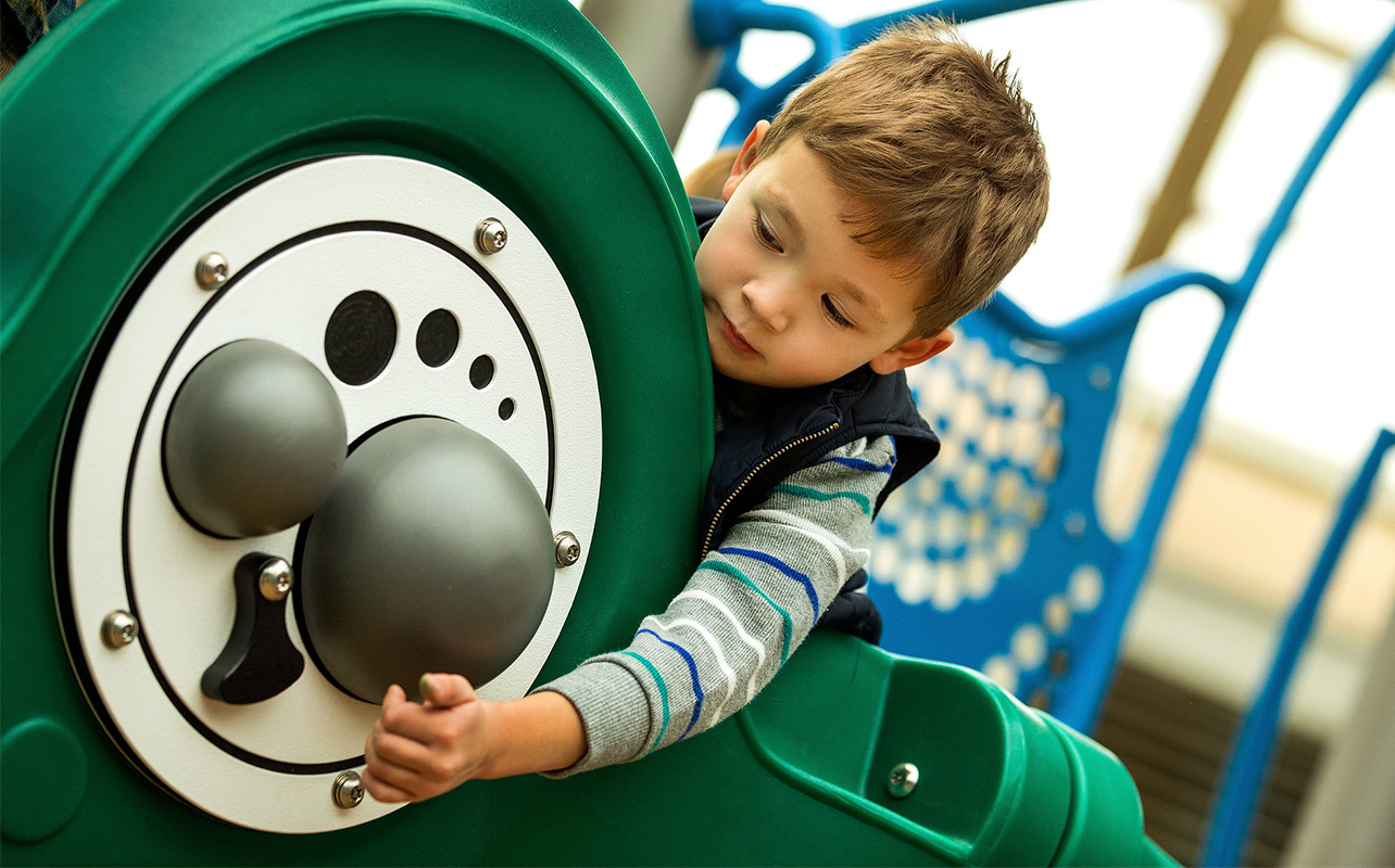 Child Playing On PlayCore Inclusive Playground Equipment