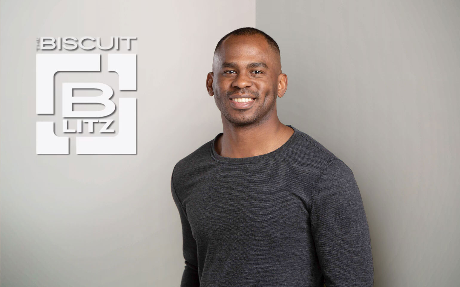 Chris Cureton in front of biscuit blitz logo