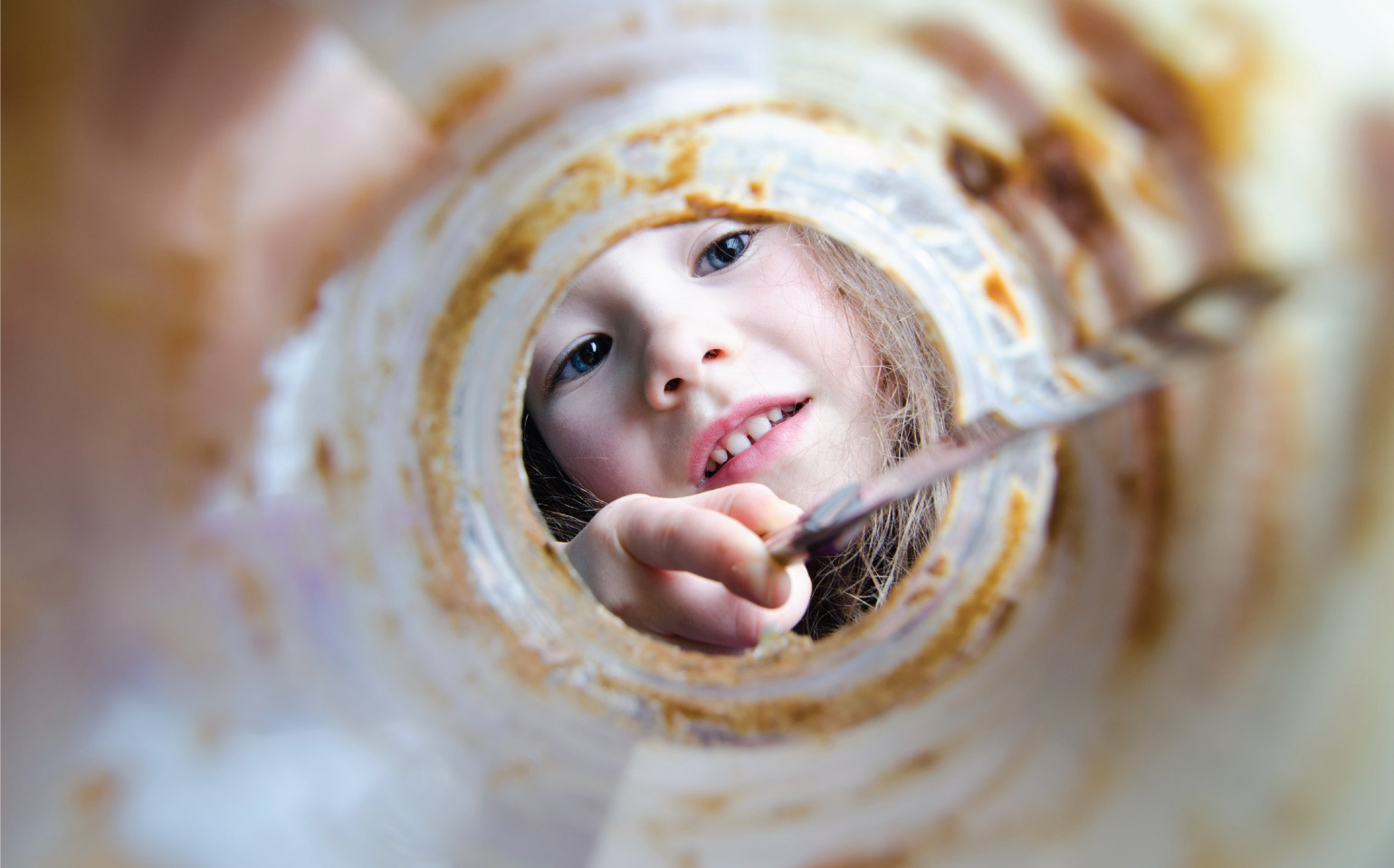 girl scraping peanut butter out of jar