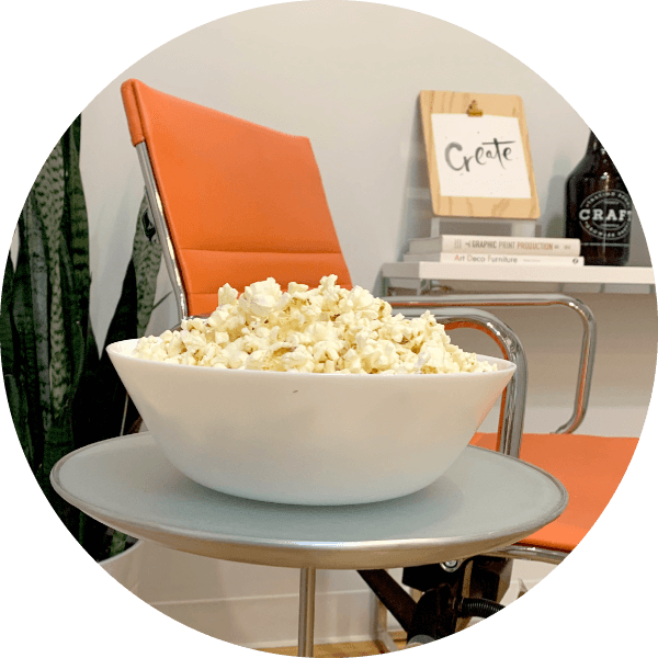 Bowl of popcorn on table by chair