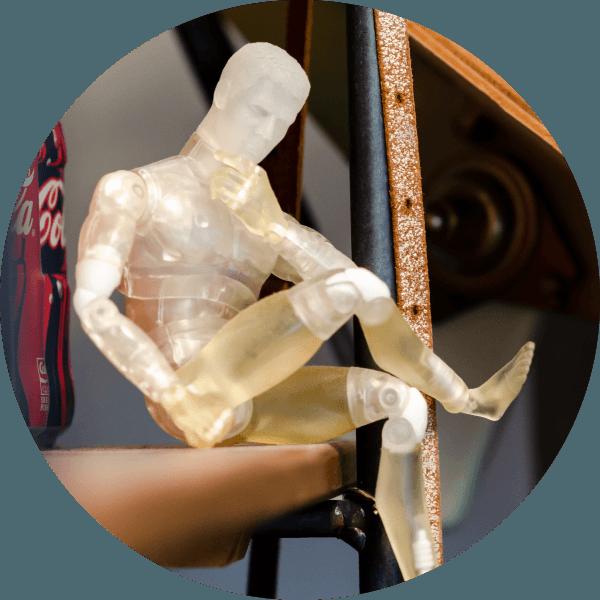 Small plastic human model sitting on shelf